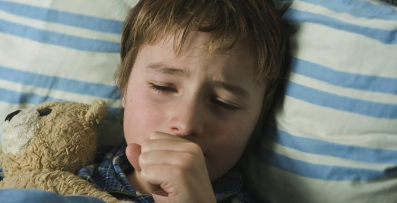Sick child coughing in bed