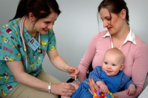 Nurse giving vaccine to baby while being held by mother